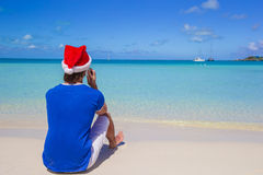 Back view of young man in santa hat with phone on Royalty Free Stock Images