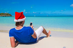 Back view of young man in santa hat with phone on Royalty Free Stock Photo
