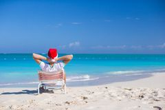 Back view of young man in santa hat relax at beach Royalty Free Stock Photos