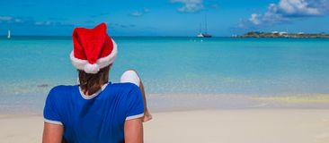 Back view of young man in santa hat on tropical Royalty Free Stock Photo