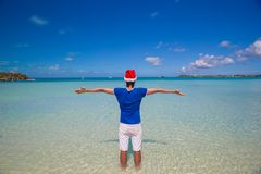 Back view of young man in santa hat on tropical Stock Image