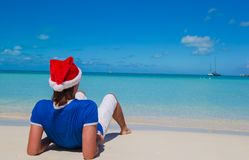 Back view of young man in santa hat on tropical Stock Photos