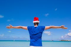 Back view of young man in santa hat on tropical Stock Images