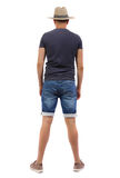 Back view of young man in shorts and hat. Stock Images