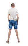 Back view of young man in shorts looking. Royalty Free Stock Photo