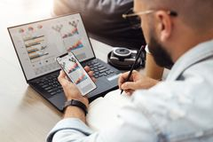 Back view. Young man sits cafe front of laptop with graphs, charts, diagrams on monitor, uses smartphone, takes notes. Back view. Young bearded hipster man stock image