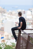 Back view of young man sitting on railings Stock Photos