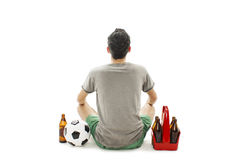 Back view of a young man with soccer ball and pack of beer looking at wall. Rear view Royalty Free Stock Image