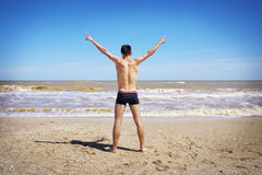 Back view of Young man spread his hands on beach. Man on beach hold hands arms up, rear view guy, standing back looking to sea blue sky horizon, vacation Stock Photo