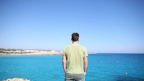 Back view of young man standing on cliff stock video