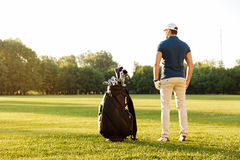 Back view of a young man standing on a green field. With golf bag Royalty Free Stock Photos