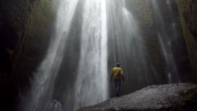 Back view of young man standing on the stone near the powerful waterfall Gljufrabui in Iceland in windy day.