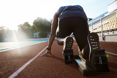 Back view of a young man in starting position for running. On sports track Stock Photo