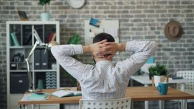 Back view of young man stretching arms relaxing sitting in office at desk alone. Back view of young man wearing shirt is stretching arms relaxing sitting in stock video footage