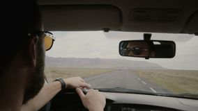 Back view of young man in sunglasses driving the vehicle, another man sitting near. Friends traveling together on car. Two men riding through the empty country stock footage