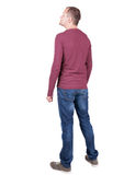 Back view of young man in t-shirt and jeans  looking. Stock Image