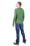 Back view of young man in t-shirt and jeans  looking. Stock Photos