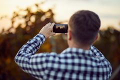 Man taking photo with digital camera on mobile phone royalty free stock photography