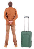 Back view of young man traveling with suitcas. Royalty Free Stock Photo