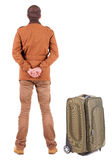 Back view of young man traveling with suitcas. Royalty Free Stock Image