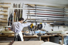 Back view of young man using circular saw in workshop Stock Photo