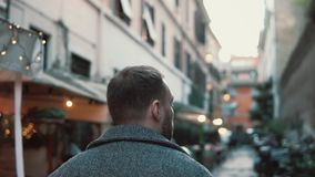 Back view of young man walking at city street in Europe. Stylish guy exploring the old town alone, looking around. Back view of young man walking at city street stock footage