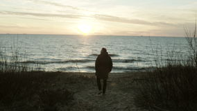 Back view of young man walking on the shore of the sea on sunset. Lonely male spending time alone in beach in cold day. stock footage