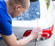 Back view of young man washing car with sponge. And soap Royalty Free Stock Photography