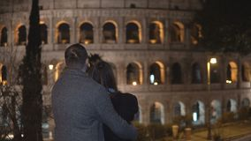 Back view of young man and woman standing near the Colosseum in Rome, Italy and hugging together.