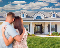 Young Military Couple Facing Beautiful New House. Back View of a Young Military Couple Facing Beautiful New House Royalty Free Stock Images