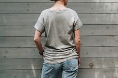 Back view. Young millennial woman dressed in gray t-shirt is stands against gray wood wall. Summer day. Back view. Young millennial woman dressed in gray t Stock Images