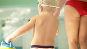 Back view of young mother and her cute little blonde child walking near swimming pool. Happy mom spending time playing. With her baby before the swimming lesson stock video footage