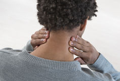 Back view of a young mulatto man with neck pain Royalty Free Stock Images