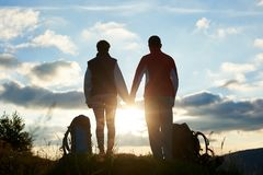 Back view of young persons admiring the sunset in mountains holding hands. Back view of young persons admiring the sunset in the mountains holding hands. Near royalty free stock photos