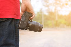 Back view of young photographer holding camera on hands with sunshine effect background. royalty free stock photography