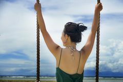 Back view of young pretty and happy Asian Chinese woman holding swing rope having fun Stock Photography