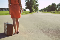 Back view of young pretty woman hitchhiking waiting along the road for a ride. On sunny outside summer background Royalty Free Stock Photography