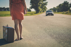 Back view of young pretty woman hitchhiking waiting along the road for a ride. On sunny outside summer background Stock Photography