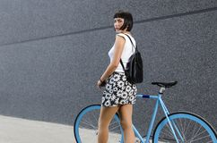 Back view, young pretty woman walking with her bicycle, Stock Image