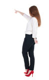 Back view of young redhead business woman pointing at wal stock photography