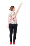 Back view of young redhead business woman pointing at wal Royalty Free Stock Photography