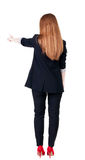 Back view of young redhead business woman pointing at wall. Stock Photography