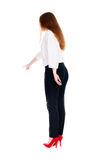 Back view of young redhead business woman pointing at wall. Stock Image