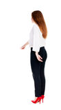 Back view of young redhead business woman pointing at wall. Stock Images