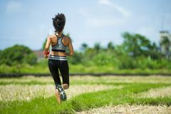 Back view of young runner woman with attractive and fit body in running outdoors workout at beautiful off road track green landsca. Pe background jogging in royalty free stock images