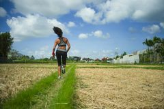 Back view of young runner woman with attractive and fit body in running outdoors workout at beautiful off road track green landsca. Pe background jogging in stock photography