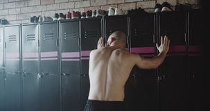Back view young shirtless muscular male athlete closing locker door, walking to window depressed after failure in gym. Athletic weight lifter sportsman feeling stock video