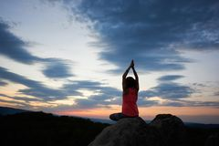 Back view of young slim athletic woman sitting on big rock in yoga pose with raised arms royalty free stock photo
