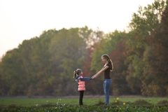Back view of young slim attractive mother and child girl standing in green meadow holding hands outdoors on forest trees blurred. Background royalty free stock images
