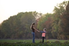 Back view of young slim attractive mother and child girl standing in green meadow holding hands outdoors on forest trees blurred stock photo